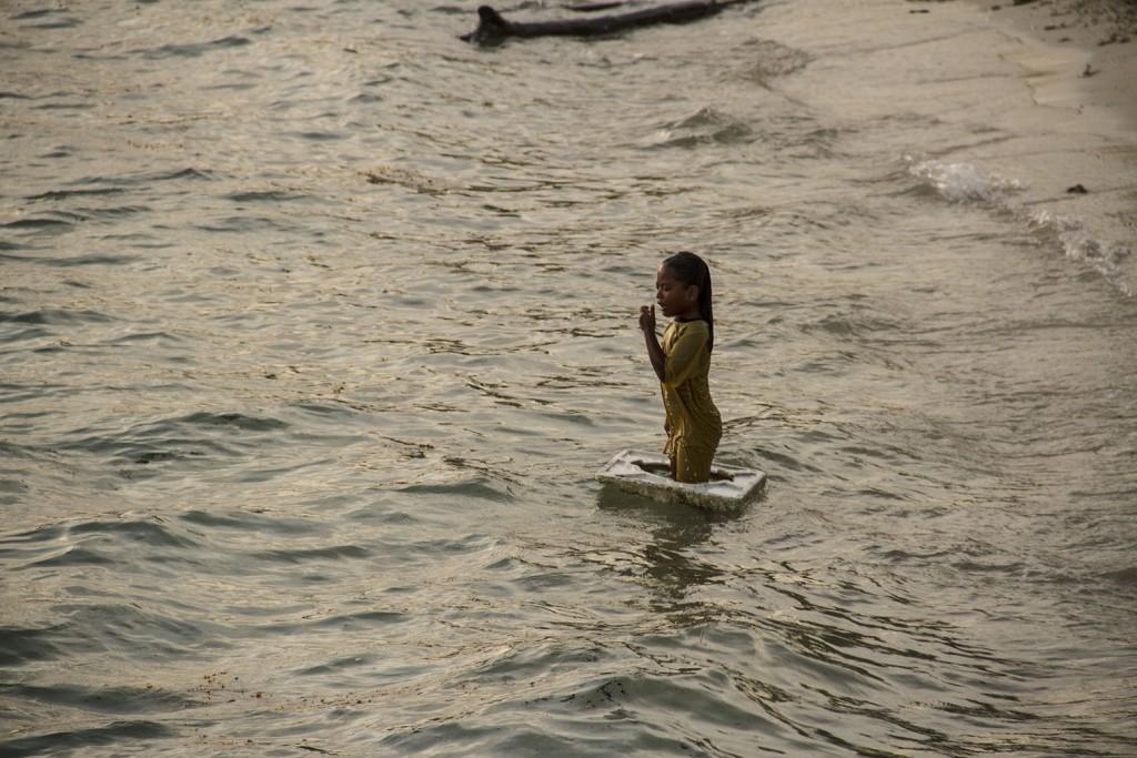Al atardecer, los niños utilizan la basura flotante como juguetes